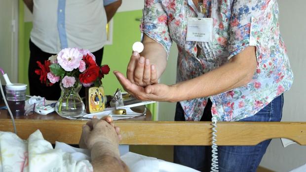 25 Juin 2013 : Olivia DUJARDIN est une laïque aumônier de l'Hôpital Saint Vincent de Paul ( Groupement des Hôpitaux de l'Institut Catholique de Lille). Formée au CIPAC (Centre interdiocésain de formation pastorale et catéchétique) elle a reçu une lettre de mission de l'évêque de Lille et elle est rémunérée par l'hôpital. Ici, elle vient porter la communion à une malade en fin de vie dans l'Unité de Soins Palliatifs de ce même hôpital. Lille (59) France.  June 2013 : Volunteers accompany patients at end of life in the Palliative Care Center of the St Vincent de Paul hospital. Lille (59), France.