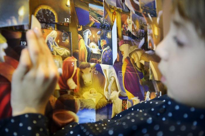 21 décembre 2014 : Illustration de l'Avent. Jeune garçon devant un calendrier de l'Avent, France. December 21, 2014 : Christmas illustration. France.