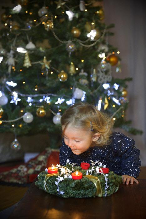 21 décembre 2014 : Illustration de l'Avent. Fillette de 2 ans et demi et couronne de l'Avent, France. December 21, 2014 : Christmas illustration. France.
