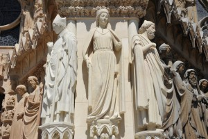 """Statue restaurée de la Reine de Saba aux côtés de Saint Rigobert et de « l'Homme à la tête d""""Ulysse », ornant l'éperon nord de la façade occidentale de la Cathédrale de Reims."""