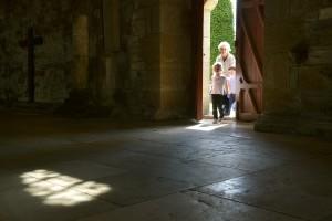 23 avril 2014 : Une grand-mère et ses petits enfants entrant à l'intérieur de la basilique de Vézelay. Vézelay (89), France.