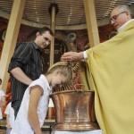 05 juin 2011: Geste de l'eau lors du baptême de Julia par le P. Laurent CROS, en présence de son parrain, Paroisse sainte Thérèse d'Annecy (74), France.