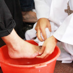 Un évêque lavant les pieds d'un homme, comme Jésus a lavé les pieds de ses apôtres.