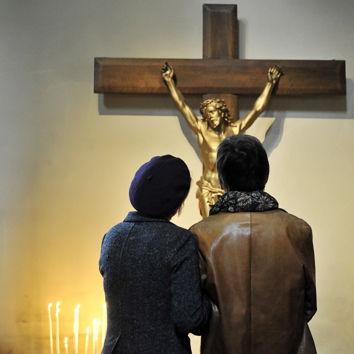 10 novembre 2013 : Couple dans une église se recueillant devant un Christ en croix. Paris (75), France. November 10, 2013: Couple praying in front of the Christ on the cross. Church of Our Lady of the Nativity of Bercy, in Paris, France.