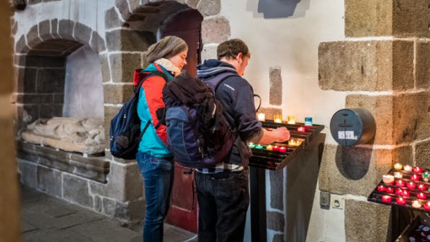 29 mars 2016 : Un couple de touristes allemands allume une bougie dans l'église Saint Pierre. A la fois sanctuaire et église du Mont, cette petite église située en haut de la rue principale a assuré au cours des siècles la permanence de la prière chrétienne et de la dévotion à Saint-Michel sur le Mont. Le Mont Saint-Michel (50), France