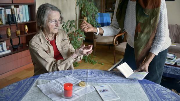 14 mai 2015 : Une laïque apporte la communion à domicile. Paris (75), France.
