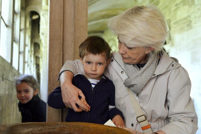 23 avril 2014 : Une grand-mère faisant le signe de croix avec son petit-fils de 3 ans, cloître de la basilique de Vézelay. Vézelay (89), France. April 23, 2014: Grandmother and grandchildren. Vézelay, France.