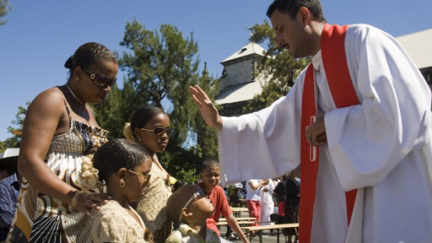 16 mars 2008 : Bénédiction d'une famille lors de la messe du Dimanche des Rameaux célébrée par le p. Jean-Bernard sur le parvis de l'égl. Sainte Jeanne-D'Arc, Le Port (97), La Réunion, France.  Palm Sunday Mass celebrated by fath. Jean-Bernard on the square of Saint Jeanne-d'Arc's church - Ville du Port, La Réunion.