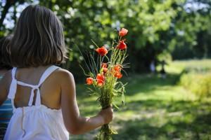 03 juillet 2014 : Promenade dans la campagne. Petite fille tenant un bouquet de coquelicots à la main. Maurecourt (95), Val d'Oise, France. July 03, 2014: A walk in the countryside. Maurecourt (95), France.