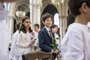 2 juin 2018 : Enfants en procession, une rose à la main, lors de la célébration des premières communions. Paroisse Saint Jean Baptiste de Belleville. Paris (75), France.