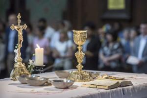 2 juin 2018 : Objets liturgiques posés sur l'autel, lors de la célébration de l'eucharistie : calice, coupelles contenant les hosties, missel d'autel et crucifix. Paroisse Saint Jean Baptiste de Belleville à Paris (75), France.