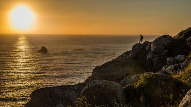 15 mai 2015 : Pèlerinage vers Saint Jacques de Compostelle. Silhouette d'un pèlerins regardant le soleil se coucher à Fisterra. Espagne.