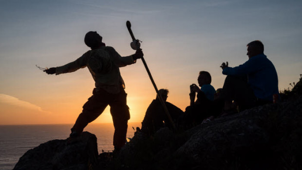15 mai 2015 : Pèlerinage vers Saint Jacques de Compostelle. Groupe de pèlerins regardant le soleil se coucher au phare de Fisterra en Galice. Camino Frances. Espagne.