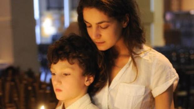 22 juillet 2014 : Une mère et ses deux enfants à léglise Sainte Marie des Batignolles, apprentissage de la prière, Paris (75), France