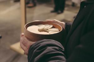 Un laïc distribue la communion au corps du Christ, au cours de la célébration eucharistique.