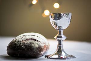 Une miche de pain et une coupe de vin symbolisant l'eucharistie. « Fidèle à l'exemple du Christ, l'Église a toujours employé le pain et le vin avec de l'eau pour célébrer le banquet du Seigneur. » PGMR n°319