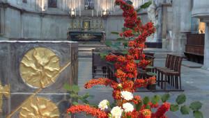 Dahlias blancs et branches de pyracantha dans une composition florale pour la Toussaint.