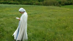 07-08 mai 2005 : Moniale des Fraternités monastiques de Jérusalem lisant la prière du jour dans un champ lors du pèlerinage sur les routes de Vézelay (89), France.